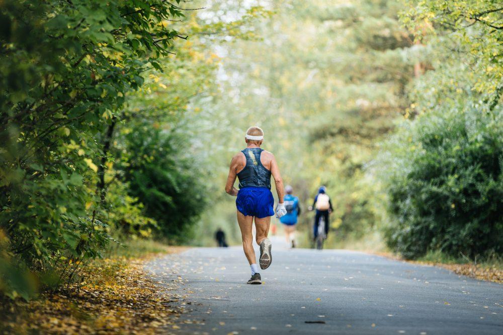 back oldest male runner marathon running in autumn Park. yellow leaves on ground